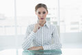 Concentrating chic businesswoman sitting thinking at her desk looking camera Royalty Free Stock Image