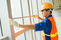 Concentration on measuring profile view of a constructor worker with a tape Royalty Free Stock Photography