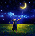 Concept of ambition and dreams realization child who takes the moon Stock Photos