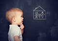 Concept baby looks at board which is drawn family and home the with chalk Royalty Free Stock Image