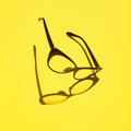 Concept background of black glasses floating above the yellow sp
