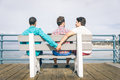 Concept about cheating in a relationship gay couple and third lover on bench Stock Photos