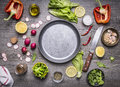 Concept cooking vegetarian food ingredients laid out around the pan with a knife spices space for text on rustic wooden backgr Royalty Free Stock Photo