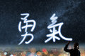 Concept of courage silhouette asian business woman light drawing the chinese words means Stock Photography