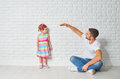 Concept dad measures growth of her child daughter at a wall the blank brick Royalty Free Stock Photography