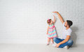 Concept dad measures growth of her child daughter at a wall the blank brick Stock Photos