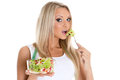Concept of dieting slender young woman with tape measure holds a bowl salad on a white background Stock Image