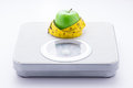 Concept of eating healthy and maintaining good body. Apple and tape measure on bathroom scale isolated on white background. Royalty Free Stock Photo