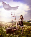 Concept fantasy dreaming about travel beautiful woman with suitcases standing near the ladder to the flying paper boat in the Stock Photos