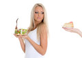 Concept of healthy food young beautiful woman choosing between bowl salad with fresh vegetables and piece cake on a white Royalty Free Stock Photography