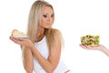 Concept of healthy food young beautiful woman choosing between bowl salad with fresh vegetables and piece cake on a white Stock Image