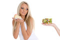 Concept of healthy food young beautiful woman choosing between bowl salad with fresh vegetables and piece cake on a white Stock Photography