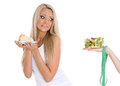 Concept of healthy food young beautiful woman choosing between bowl salad with fresh vegetables and piece cake on a white Royalty Free Stock Photo