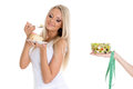 Concept of healthy food young beautiful woman choosing between bowl salad with fresh vegetables and piece cake on a white Royalty Free Stock Photos