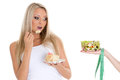 Concept of healthy food young beautiful woman choosing between bowl salad with fresh vegetables and piece cake on a white Stock Images