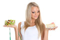 Concept of healthy food young beautiful woman holds bowl salad with fresh vegetables piece cake and tape for measuring on a white Stock Photo