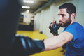 Concept of a healthy lifestyle.Hispanic muscular man fighter practicing kicks with punching black bag.Kick boxer boxing Royalty Free Stock Photo