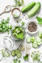 Concept of home canning. Jar of pickled cucumbers and ingredients on a light background, top view
