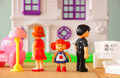 Concept image of parent busy or angry and child in the middle in front of little plastic toy dolls male female child selec Stock Photos