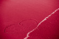 Concept of infidelity or fragile fugitive ephemeral love heart drawn in sand being washed by the sea Stock Photography
