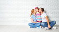Concept of mortgage housing problems family mother father child daughter at a blank white brick wall Stock Photo