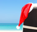 Concept of perfect vacation christmas card or background sunlounger with santa hat standing on beautiful tropical beach with white Stock Photo