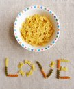 A concept photograph showing a bowl of ribbon pasta in a children bowl with the word love spelt out under it conceptual image for Stock Photos