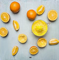 Concept of preparation of orange juice, sliced oranges, juicer  on wooden rustic background top view close up Royalty Free Stock Photo