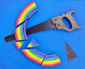 Concept rainbow cut with hand saw blue background Stock Photography
