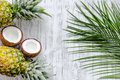 Concept of summer tropical fruits. Pineapple, coconut and palm branch on wooden table background top view