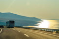 Concept of traveling to the sea tourism bus road and the seas seaside with some hills in background at sunset light reflecting Royalty Free Stock Image