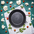Concept vegetarian food Cauliflower parsley cherry tomatoes old cast iron skillet white napkin rustic wooden background close u Royalty Free Stock Photo