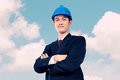 Conceptual image of leadership and reliability architect with c confident asian in formal wear posing crossed arms on blue sky Royalty Free Stock Photography