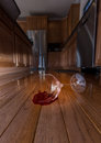 Conceptual image suggesting menace concept of domestic disturbance at home with broken wine glass on floor of modern kitchen Stock Images