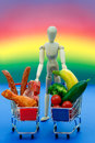 Conceptual man meat vegetables on bright rainbow background symbol holding two shopping carts one is full with and one with Stock Images