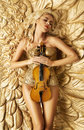 Conceptual picture of golden woman holding a violin Royalty Free Stock Photo