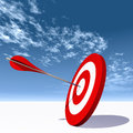 Conceptual red dart target board with arrow in the center on clouds Royalty Free Stock Photo