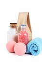 Conceptual spa still life bottles colorful bath salt blue rolled towel paper bag two pink salt balls Stock Images