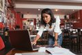 Concerned business woman female bar owner looking at laptop screen Stock Photography