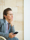 Concerned business woman holding mobile phone Stock Photography