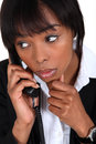 Concerned businesswoman taking phone call Stock Image