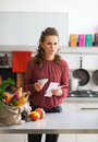 Concerned housewife in kitchen with shopping bag portrait of young and grocery checks Stock Photos