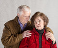 Concerned husband mature comforting depressed senior wife Stock Photos