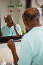 Concerned senior man touching cheek while looking into mirror Royalty Free Stock Photo