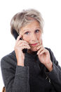 Concerned senior woman using a telephone attractive grey haired with worried expression wireless isolated on white Stock Photo