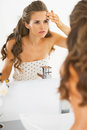 Concerned young woman checking facial skin condition in bathroom Royalty Free Stock Photos