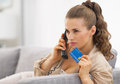 Concerned young woman with credit card talking phone in living room Royalty Free Stock Photography