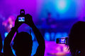 Concert recording video with a smartphone and camera at a Stock Photos