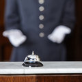 Concierge pointing to hotel bell with white gloves on counter Stock Photo