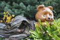 Concrete bear driftwood tree background suburban or urban outdoors landscape lawn design with cement animal critter and flowers Royalty Free Stock Photography